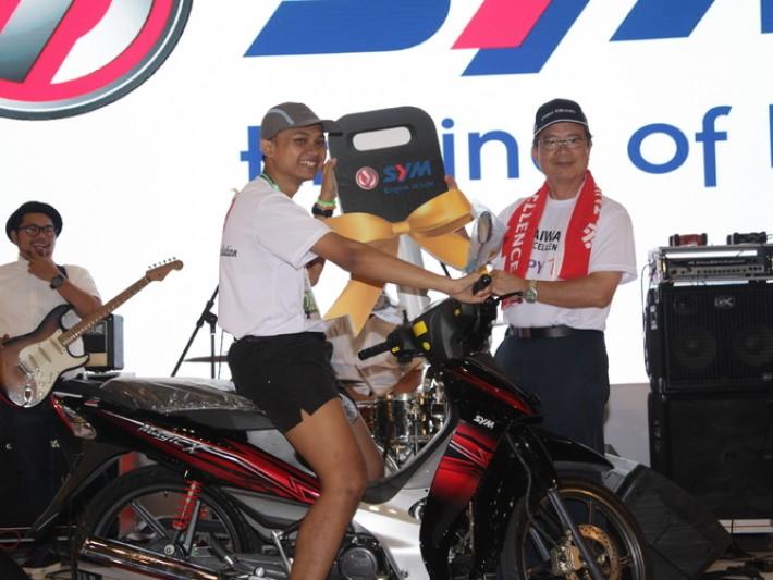 駐印尼代表處陳忠大使(右)與幸運抽中三楊機車的跑者開心合影