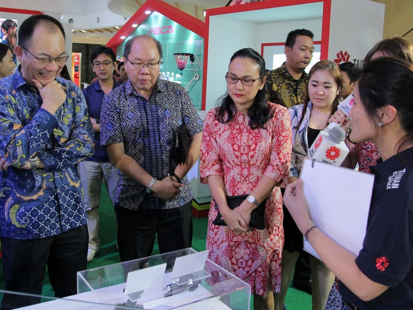 駐印尼台北經濟貿易代表處經濟組副組長廖浩志(左)帶領貴賓參觀台灣精品展示。